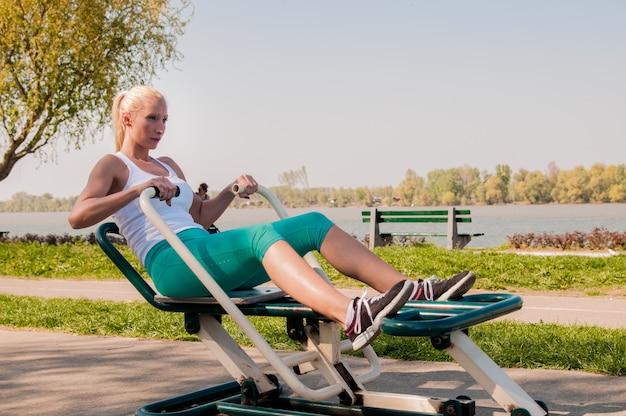 Forte garota em terno de treino trabalhando na academia ao ar livre. conceito de fitness e estilo de vida saudável.