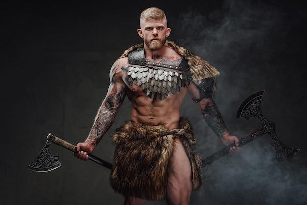 Forte guerreiro tatuado em armadura leve e pele com dois machados no escuro