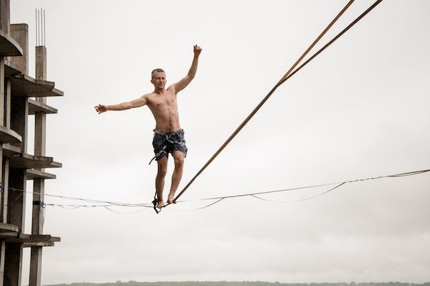 Forte homem corajoso, equilibrando-se em um slackline alto contra céu e prédio vazio