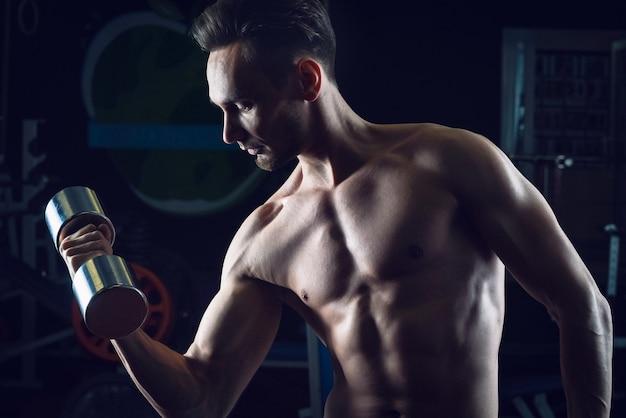 Forte homem musculoso com torso nu malhando na academia fazendo exercícios com dumbell