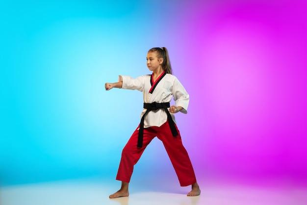 Forte. karatê, garota de taekwondo com faixa preta isolada em fundo gradiente em luz de néon. pequeno modelo caucasiano, garoto do esporte, treinamento em movimento e ação. esporte, movimento, conceito de infância.