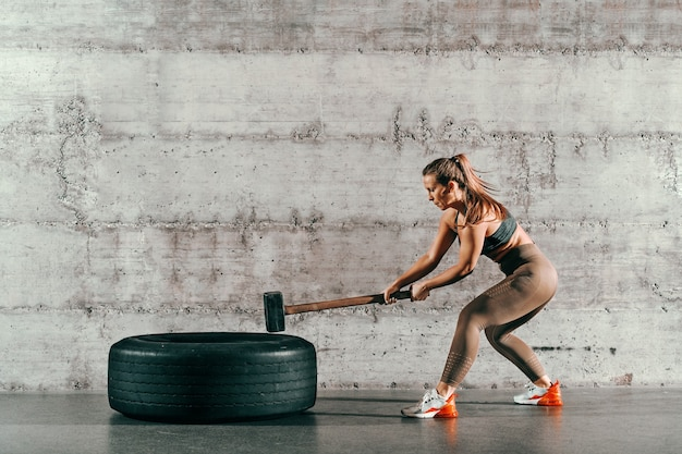 Forte morena musculosa caucasiana com rabo de cavalo e em sportswear bater o pneu com o martelo na frente da parede cinza no ginásio.