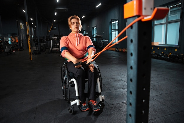 Forte. mulher com deficiência treinando no ginásio do centro de reabilitação, praticando. mulher ativa com deficiência. conceito de estilo de vida saudável, motivação, concentração, inclusão e diversidade.