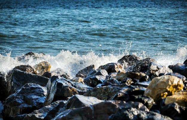 Forte onda de mar bate nas rochas.