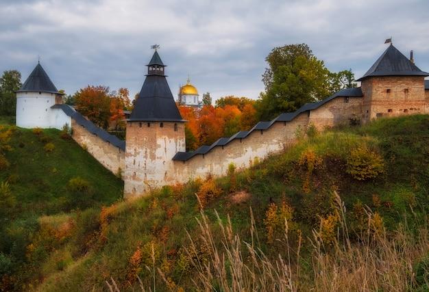 Fortes muralhas defensivas e belas igrejas nas colinas do mosteiro dormition pskovo pechersky, na cidade de pechery, região de pskov, rússia durante o outono dourado