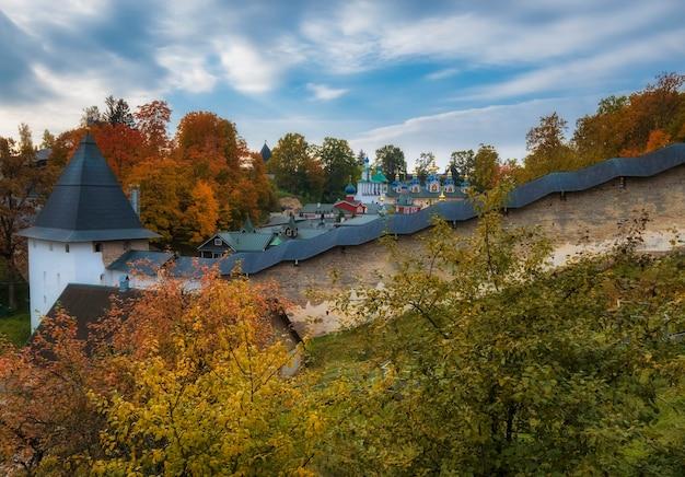 Fortes muralhas defensivas e belas igrejas no mosteiro dormition pskovo pechersky, na cidade de pechery, região de pskov, rússia durante o outono dourado