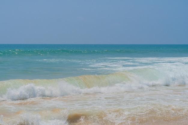 Fortes ondas costeiras na costa arenosa do oceano.