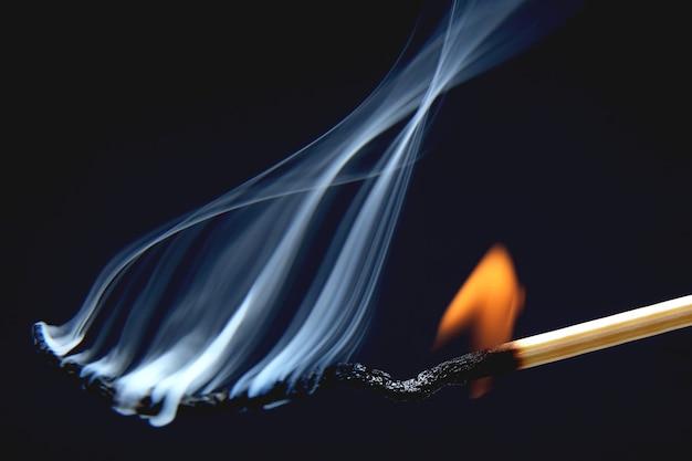 Fósforo aceso em um fundo azul escuro. fonte de fogo