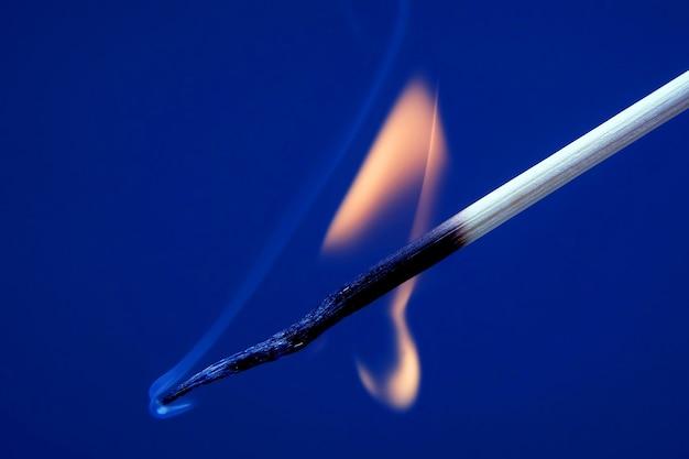Fósforo aceso em um fundo azul. fonte de fogo