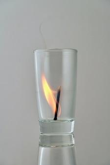 Fósforo aceso em um vidro transparente sobre um fundo claro