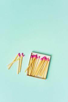 Fósforos de madeira brilhantes espalhados de caixa de fósforos em um fundo de cor pastel turquesa