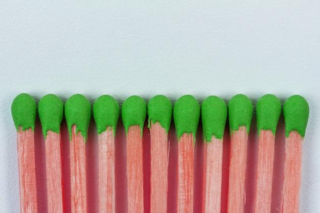 Fósforos de madeira rosa com enxofre verde em cinza