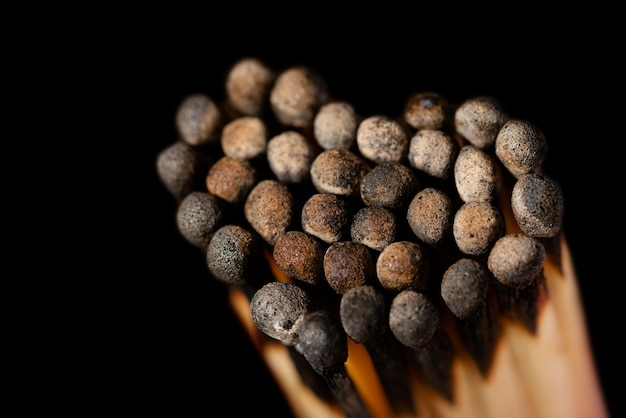 Fósforos pretos queimados em forma de coração em fundo escuro