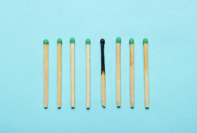 Fósforos queimados e inteiros em uma mesa azul. conceito de minimalismo