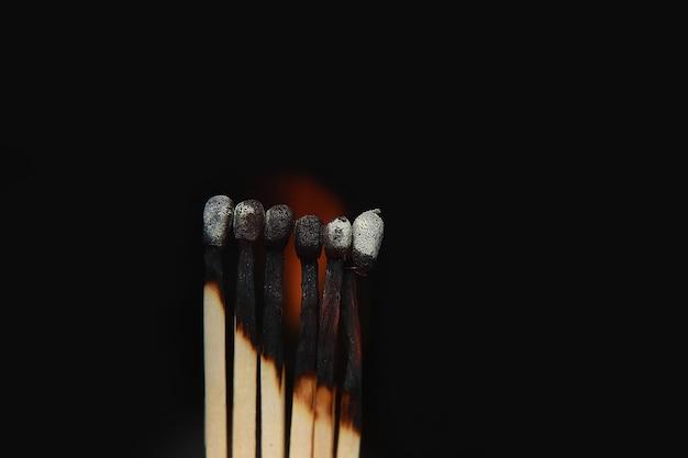 Fósforos queimados em fundo preto.