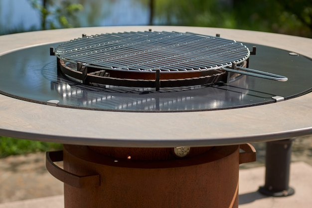 Fossa de grelha de chaleira com grelha de ferro fundido com chamas em volta da mesa de cozinha com superfície de churrasco quente no quintal