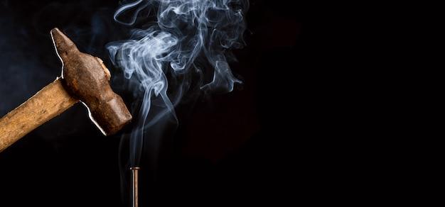 Foto abstrata do martelo oxidado do metal acima do prego com fumo no fundo preto.
