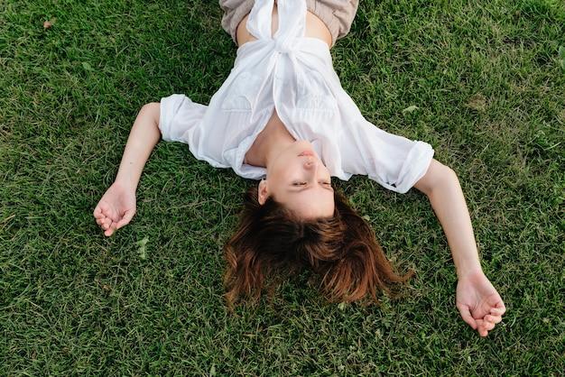Foto acima de mulher deitada na grama verde