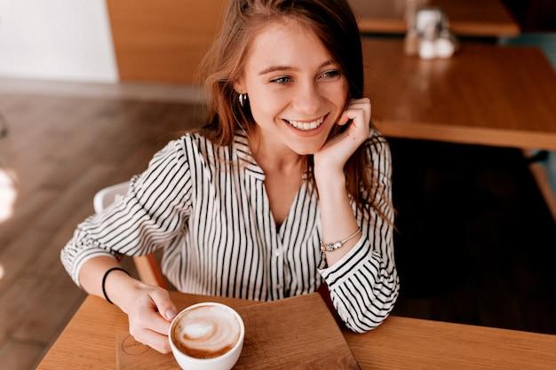 Foto acima de uma linda garota linda em uma blusa da moda