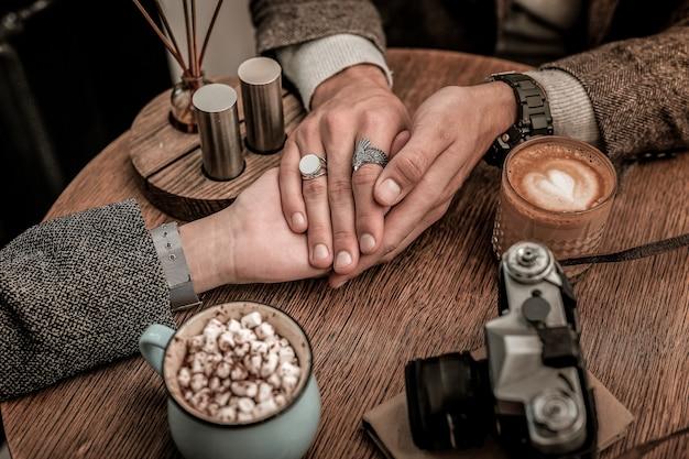 Foto aconchegante. homem segurando as mãos de uma mulher com amor no café