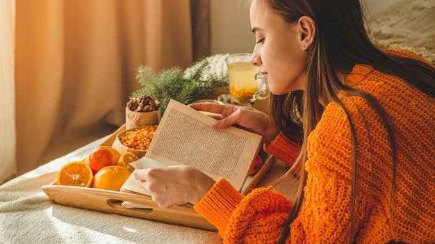 Foto aconchegante suave de mulher de suéter laranja quente na cama com uma xícara de chá e livro.
