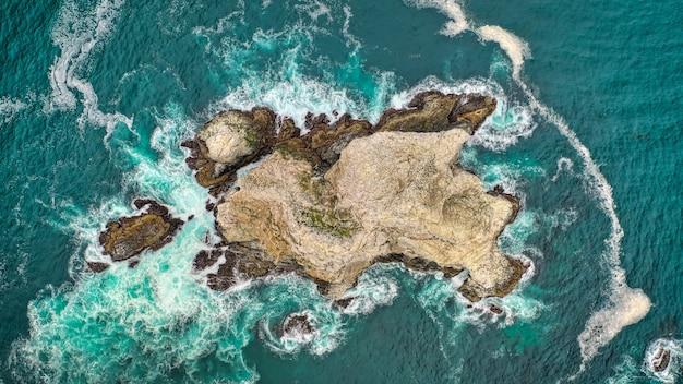 Foto aérea aérea bonita de recifes de coral no meio do oceano, com incríveis ondas do oceano