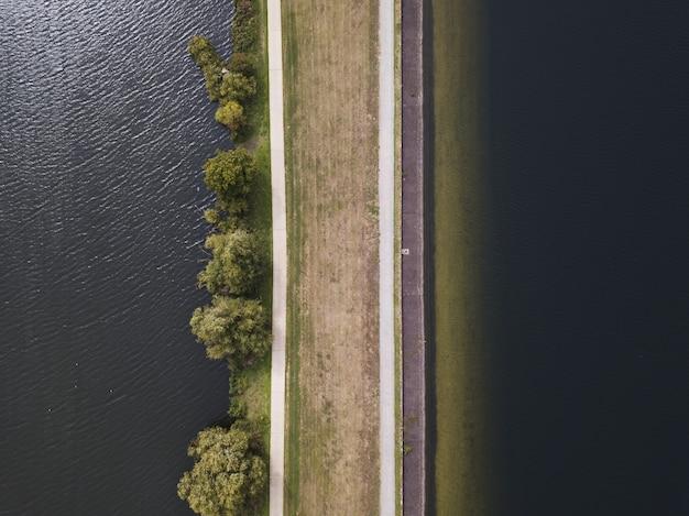 Foto aérea aérea de uma estrada marrom perto do corpo de água durante o dia