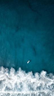 Foto aérea aérea vertical das belas ondas do mar com um avião voando acima