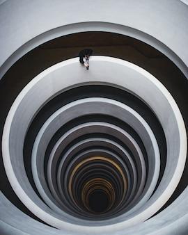 Foto aérea bonita de uma escada em espiral com um fotógrafo tirando uma foto da abertura