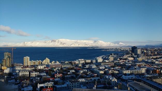 Foto aérea da cidade costeira de reykjavik com montanhas cobertas de neve em um céu azul