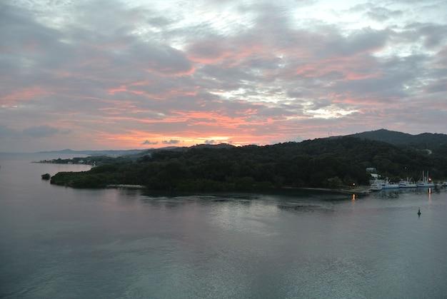 Foto aérea da costa de uma ilha coberta por florestas durante o pôr do sol