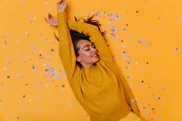 Foto aérea da garota despreocupada deitada sobre confete com um sorriso. foto interna da elegante modelo morena com suéter amarelo.