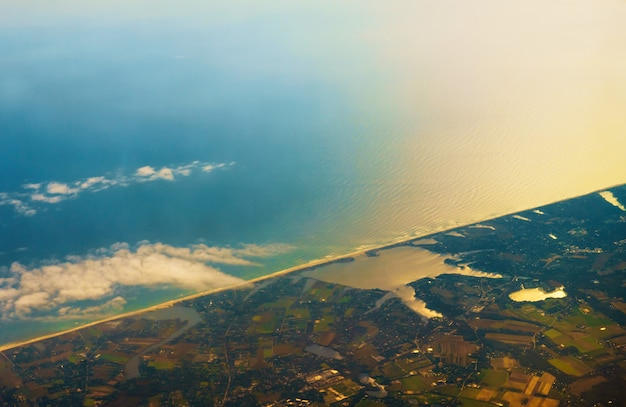 Foto aérea da paisagem e da costa ao redor da baía estendendo-se até o horizonte durante o nascer do sol pela manhã com arco-íris