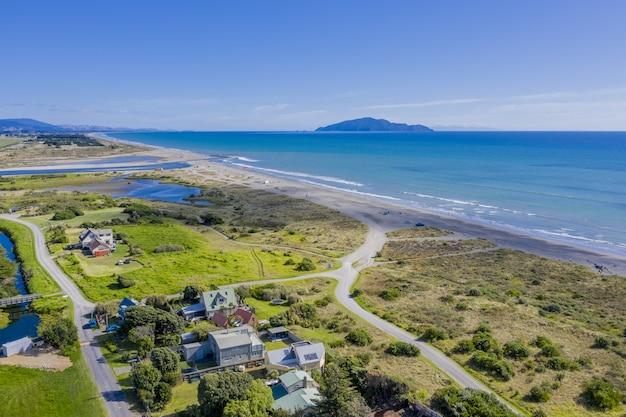 Foto aérea da praia de otaki na nova zelândia, mostrando a ilha kapiti à distância
