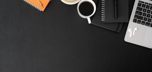 Foto aérea da sala de escritório na moda com material de escritório de computador portátil e espaço de cópia na tabela preta