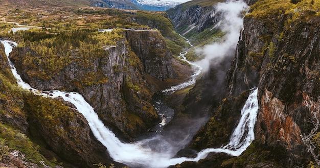 Foto aérea das belas cachoeiras sobre as montanhas, capturada na noruega