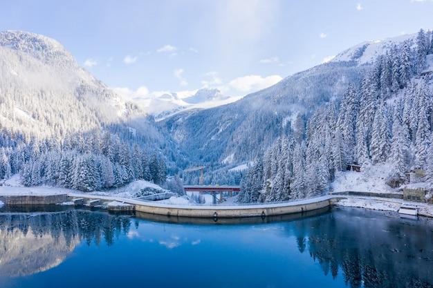 Foto aérea das montanhas cobertas de neve com um lago calmo durante o dia