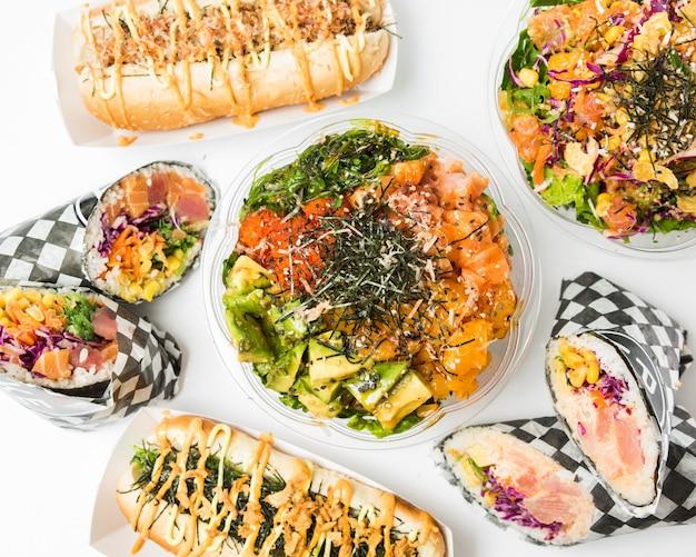 Foto aérea de alimentos e acompanhamentos em uma superfície branca