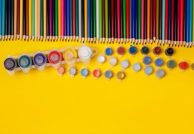 Foto aérea de artigos de papelaria em papel amarelo. quadro de material escolar