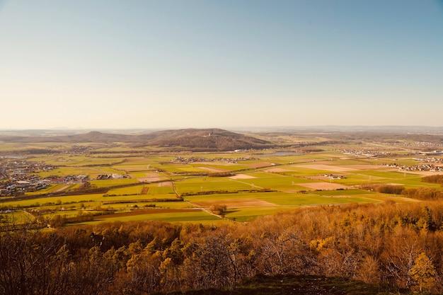 Foto aérea de campos agrícolas e uma pequena cidade cercada por colinas cobertas de vegetação