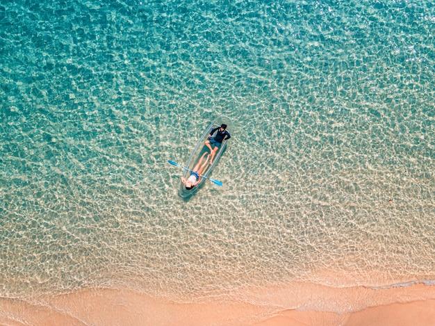 Foto aérea de casal relaxando em um caiaque praia de verão e água azul do mar