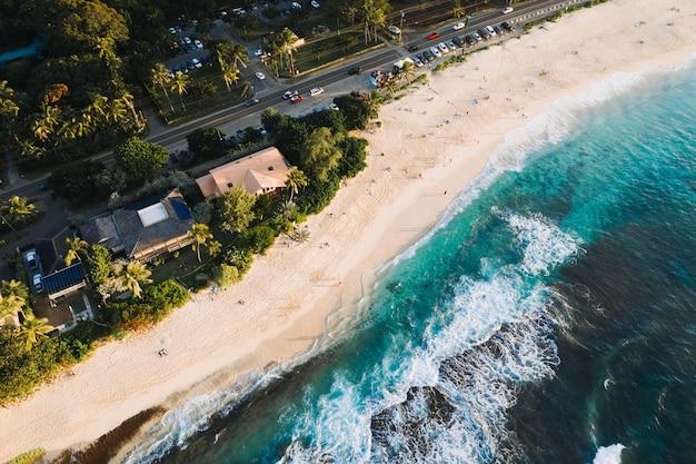 Foto aérea de casas e estradas perto da praia arenosa