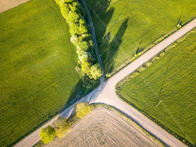 Foto aérea de drones de prados verdes e interseção de estradas de terra