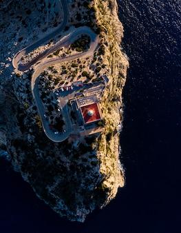 Foto aérea de falésias com uma torre no topo no meio do oceano