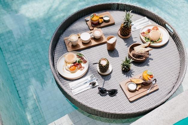Foto aérea de frutas e doces na piscina. xícara de café e abacaxi em pé na mesa.