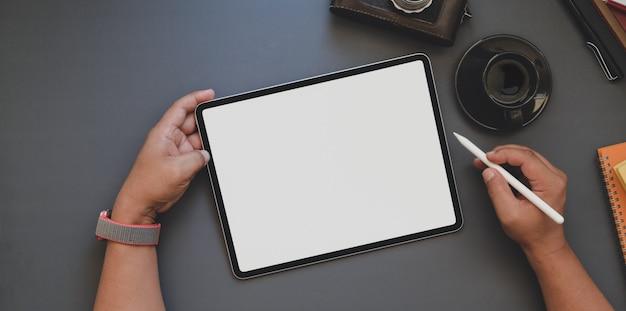 Foto aérea de jovem trabalhando no tablet de tela em branco no espaço de trabalho na moda escuro