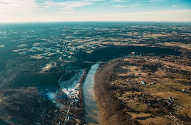 Foto aérea de lindas estradas, rios e campos com um céu azul ensolarado