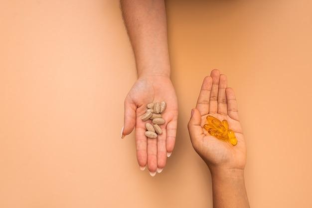 Foto aérea de mãos cheias de drogas em um fundo laranja