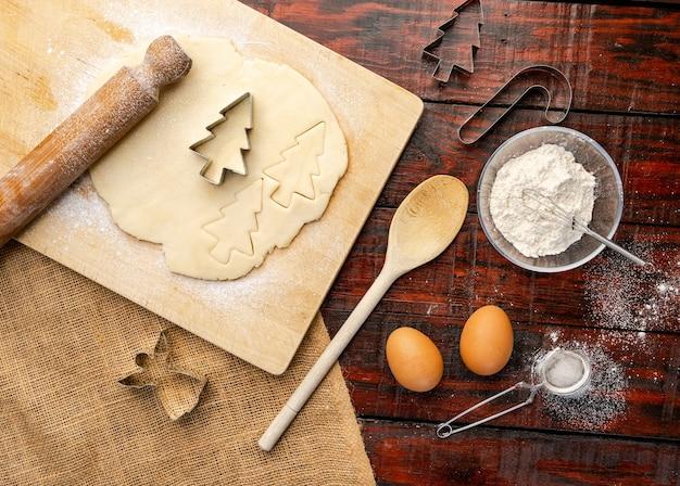 Foto aérea de massa crua e cortadores de biscoitos de natal na mesa da cozinha rústica