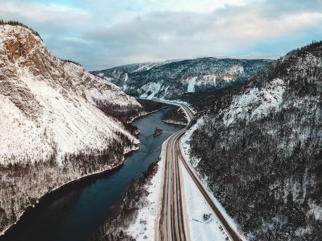 Foto aérea de montanhas cobertas de neve perto do corpo de água